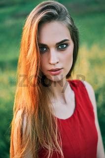Portrait of beautiful young woman posing outdoors in summer sun