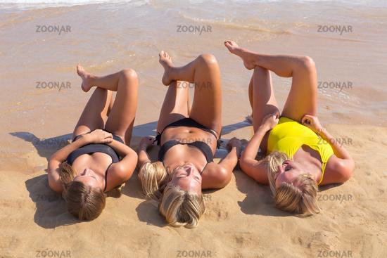 Three european girls sunbathing on beach
