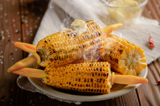 Wooden table with deep grilled sweet corn cobs under melting butter with plastic holder on clay dish