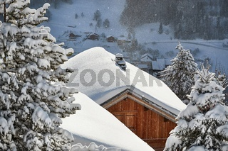 Winter mountain village, roof and chimney covered with snow