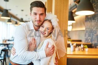 Junger Mann umarmt seine Freundin mit Brautschleier