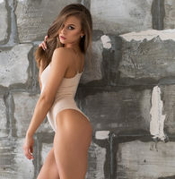Gorgeous sexy blonde in beige body by stone wall