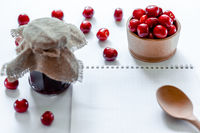 Red ripe cherries with jam jar, wooden spoon and notebook on white background. Flat lay. Food concept.