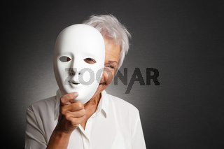 happy senior woman peeking from behind mask