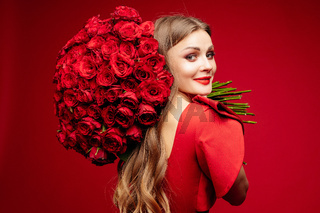 Beautiful young brunette lady in red with bunch of red roses on shoulder.