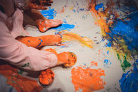 Kid hands and feet covered in colorful paintings on a paper carpet