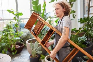 Junger Mann als Gärtner oder Florist mit Leiter
