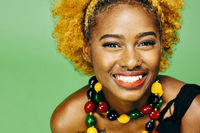 Close up of a very happy young girl with big smile and colorful necklace, in front of a green background