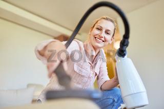 Hausfrau als Putzfrau mit Handstaubsauger