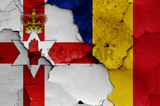 flags of Northern Ireland and Romania painted on cracked wall