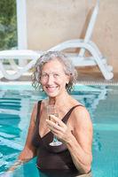 Senior Frau im Pool mit einem Sektglas