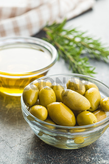 Green olives and olive oil in glass bowl.