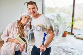 Glückliches Paar als Heimwerker beim Malern