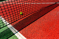 A tennis ball on the textured floor of a red court near the net after losing a match point.