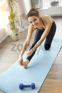 Smiling woman in sportswear exercising on fitness mat and in living room