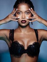 Portrait of sensual woman wearing black bra posing over blue wall background