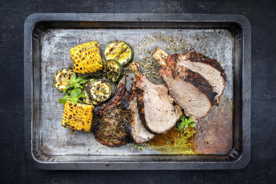 Traditional barbecue veal back racks carree roast with corn and zucchini as top view on an old griddle