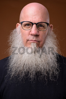Mature bald man with long gray beard against brown background