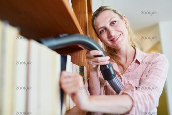 Putzfrau beim Enstauben von Bücherregal