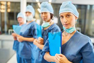 Junge Ärztin in blauer OP-Kleidung mit ihrem Team
