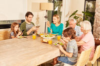 Familie am Esstisch mit Tablet und Smartphones