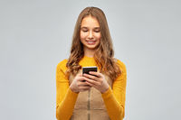 smiling teenage girl using smartphone