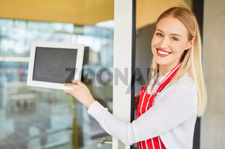 Bedienung hängt leeres Schild an Restaurant