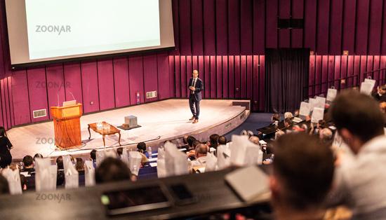 Speaker giving presentation on business conference event.