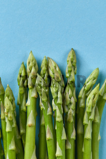 bunch of fresh asparagus stems isolated on blue