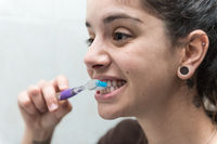 Young woman brushes her white teeth with a toothbrush.