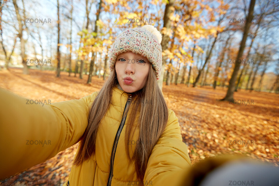 girl taking selfie making duck face at autumn park