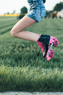 Teenage girl having fun rollerskating, jumping, spending time outdoors