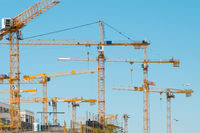 many cranes on building site - construction cranes on blue sky  -