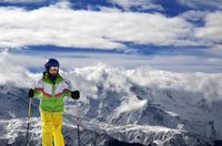 Young skier with ski poles in snowy mountains at sun winter day