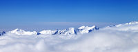 Panoramic view on high snowy mountains in clouds