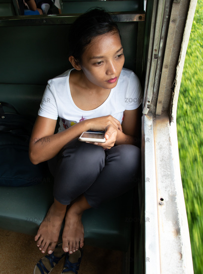 A young woman is looking out of the window of a moving train.