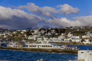 Mykonos moored ships against Greek island landscape background.