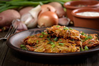 Fresh homemade tasty potato pancakes in clay dish with vegetables on wooden table