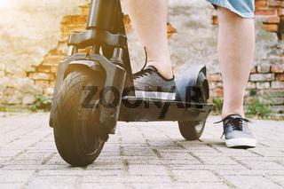 legs of unrecognizable person with electric kick scooter or e-scooter