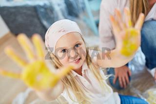 Kind zeigt bunte Hände bei der Renovierung