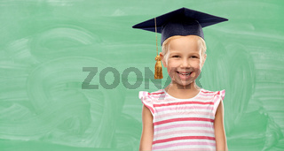 happy school girl in bachelor hat or mortarboard