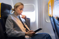 Woman reading on digital e-reader while traveling by airplane.