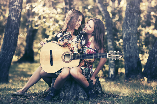 Two young fashion girls with guitar in summer forest