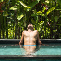 Man relaxing in outdoor spa infinity swimming pool surrounded with lush tropical greenery of Ubud, Bali.