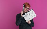 redhead woman holding movie  clapper on pink background