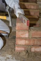 Mason works with support of spirit level and mason hammer - close-up
