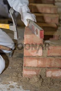 Maurer arbeitet mit Unterstützung von Wasserwaage und Maurerhammer - Nahaufnahme