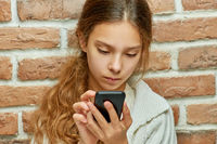 Teenager girl with long hair is typing message on mobile phone
