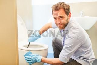 Hausmann putzt das Klo oder WC im Badezimmer