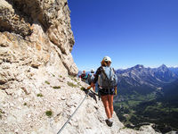 group of mountain climbers on a steep Via Ferrata with a grandiose view of the Italian Dolomites